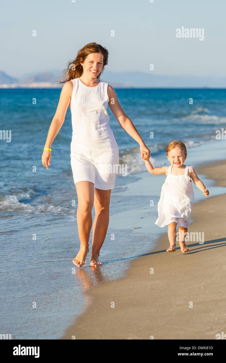 Madre e hija caminando por la playa Imagen De Stock