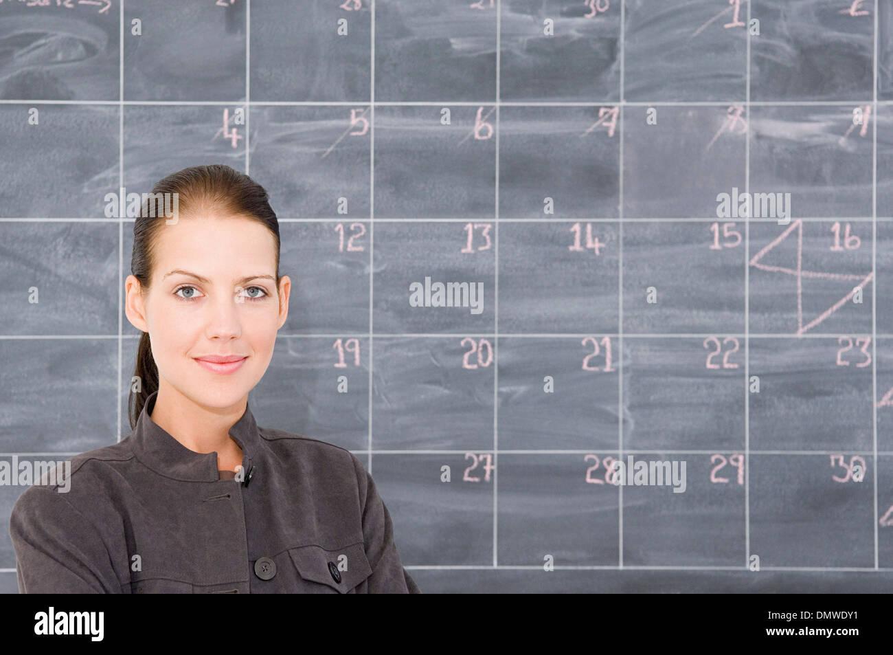 Una joven mujer delante de una pizarra, señalado como una calandria. Imagen De Stock