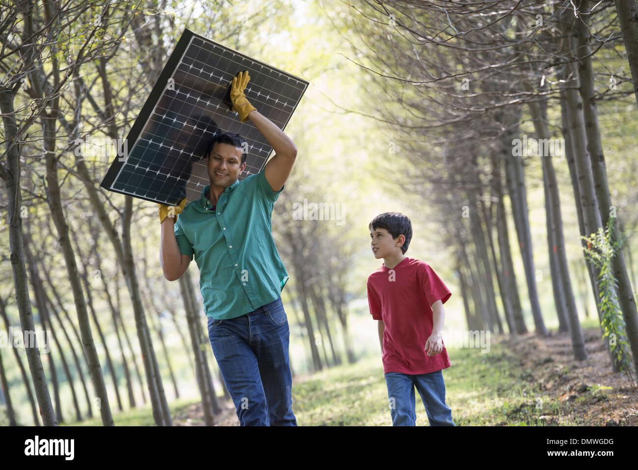 Un hombre que lleva un panel solar en una avenida de árboles acompañados por un niño. Imagen De Stock