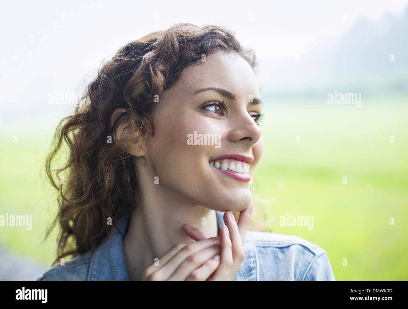 Una joven en un paisaje rural con el cabello rizado de viento. Apartar la mirada en la distancia. Imagen De Stock