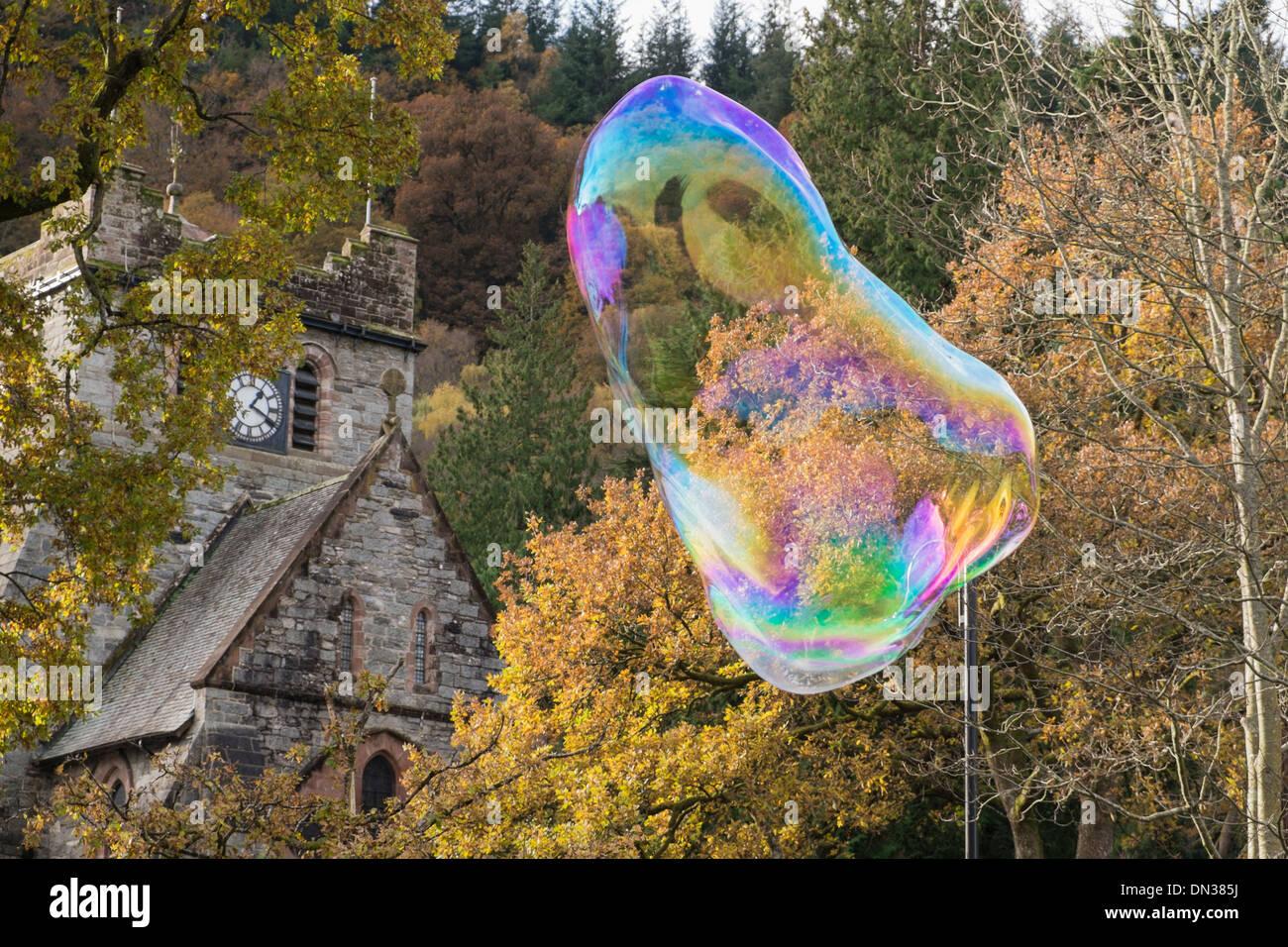Una gigantesca burbuja de jabón que muestra los colores del arco iris que flota en el aire hacia la torre del reloj de la iglesia en Betws-y-Coed, al norte de Gales, Reino Unido, Gran Bretaña Imagen De Stock