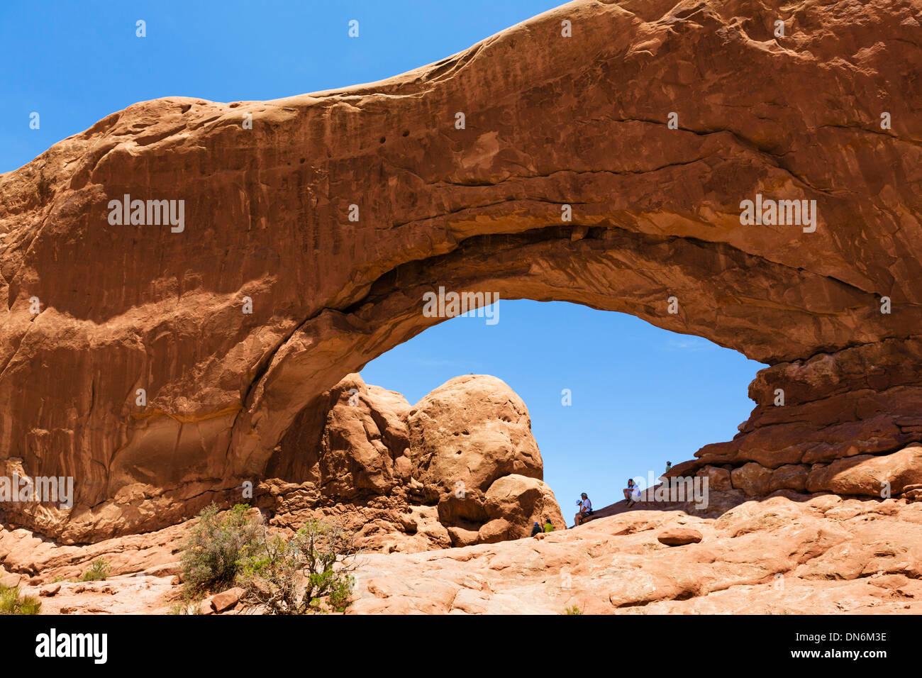 Turistas en la ventana Norte arch, la sección Windows, Parque Nacional Arches, en Utah, EE.UU. Imagen De Stock