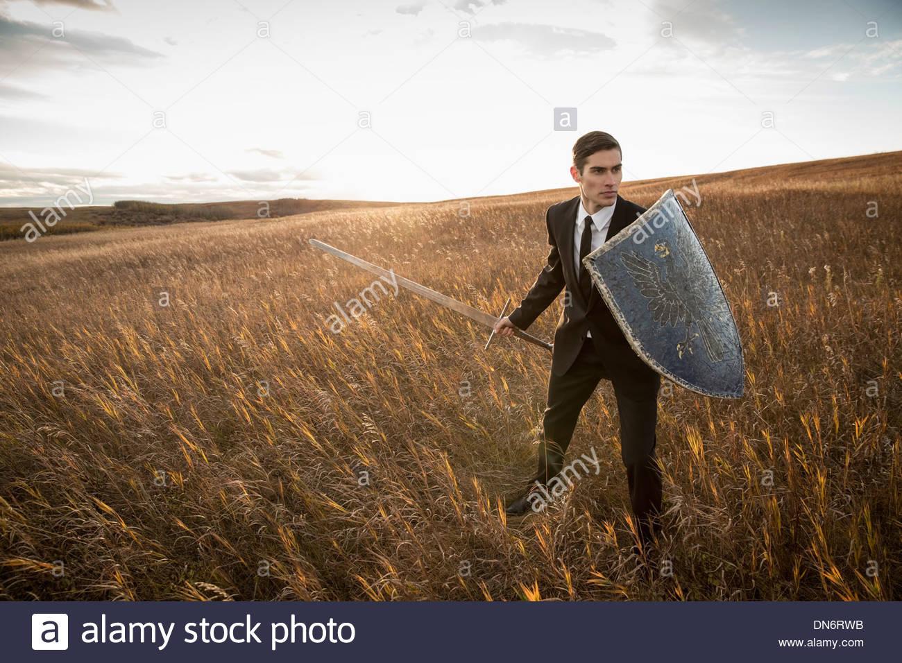 Empresario de alerta con la espada y el escudo exterior Imagen De Stock