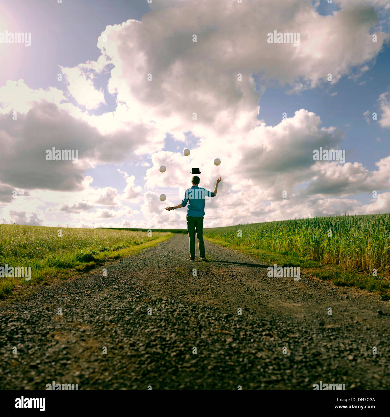 Joven con sombrero flotante haciendo malabarismos en el campo Foto de stock