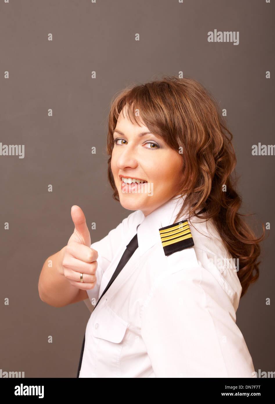 Hermosa piloto de línea aérea en uniforme con epauletes mostrando pulgar arriba gesto de aprobación Imagen De Stock