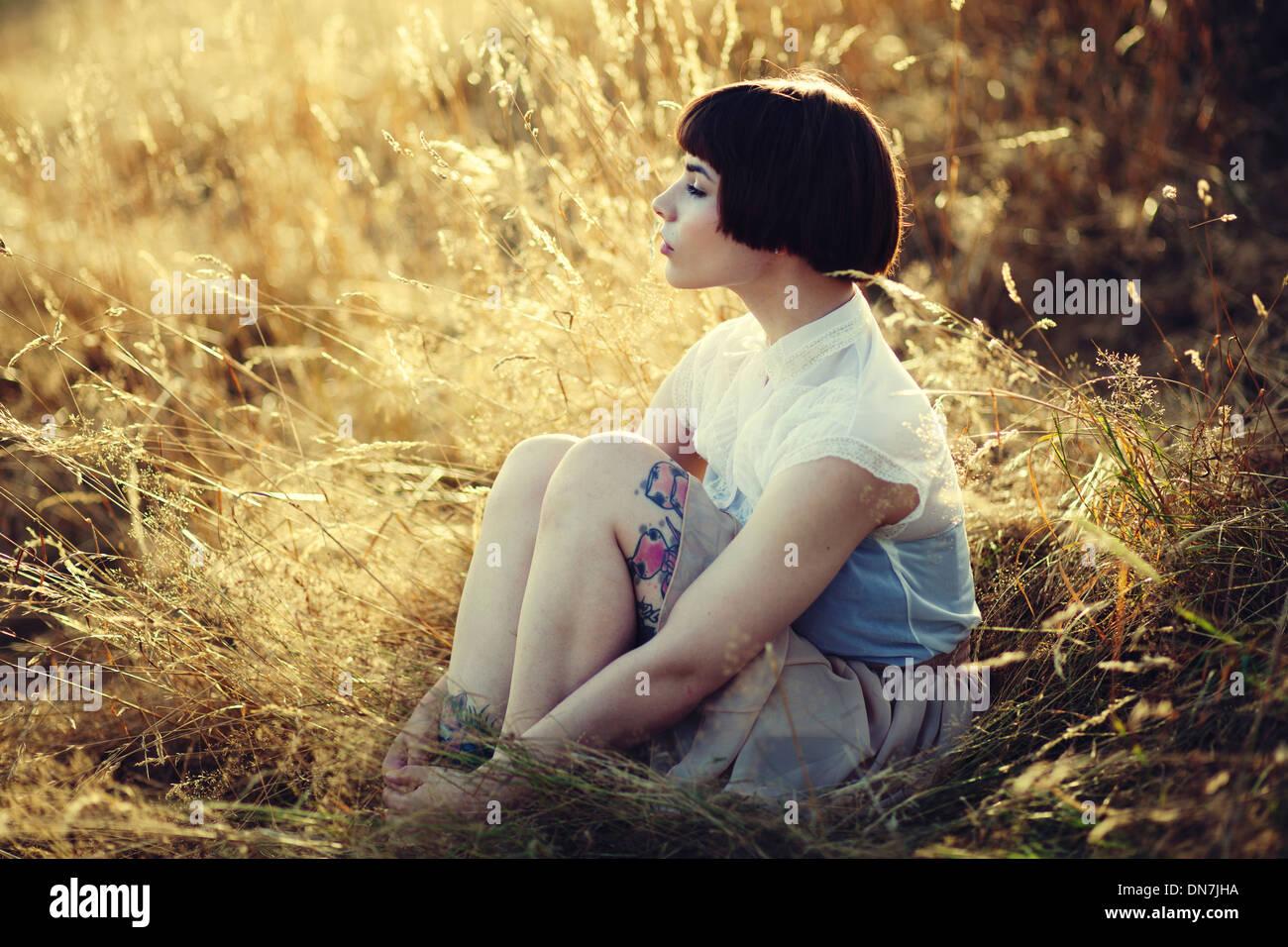 Mujer joven sentada sobre una pradera, Retrato Foto de stock