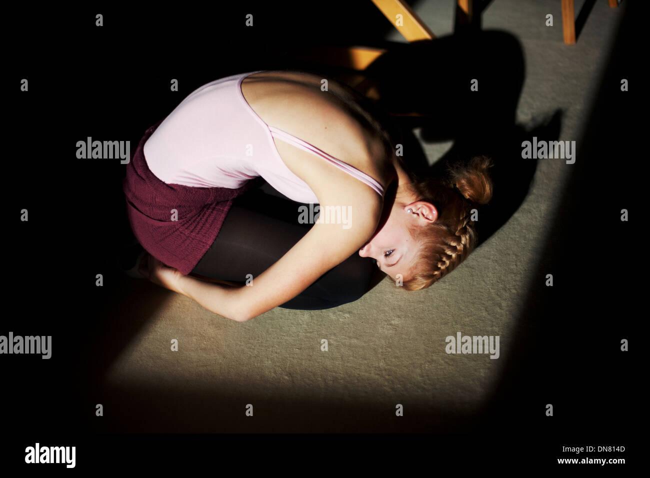 Mujer joven arrodillados en el suelo, Retrato Imagen De Stock