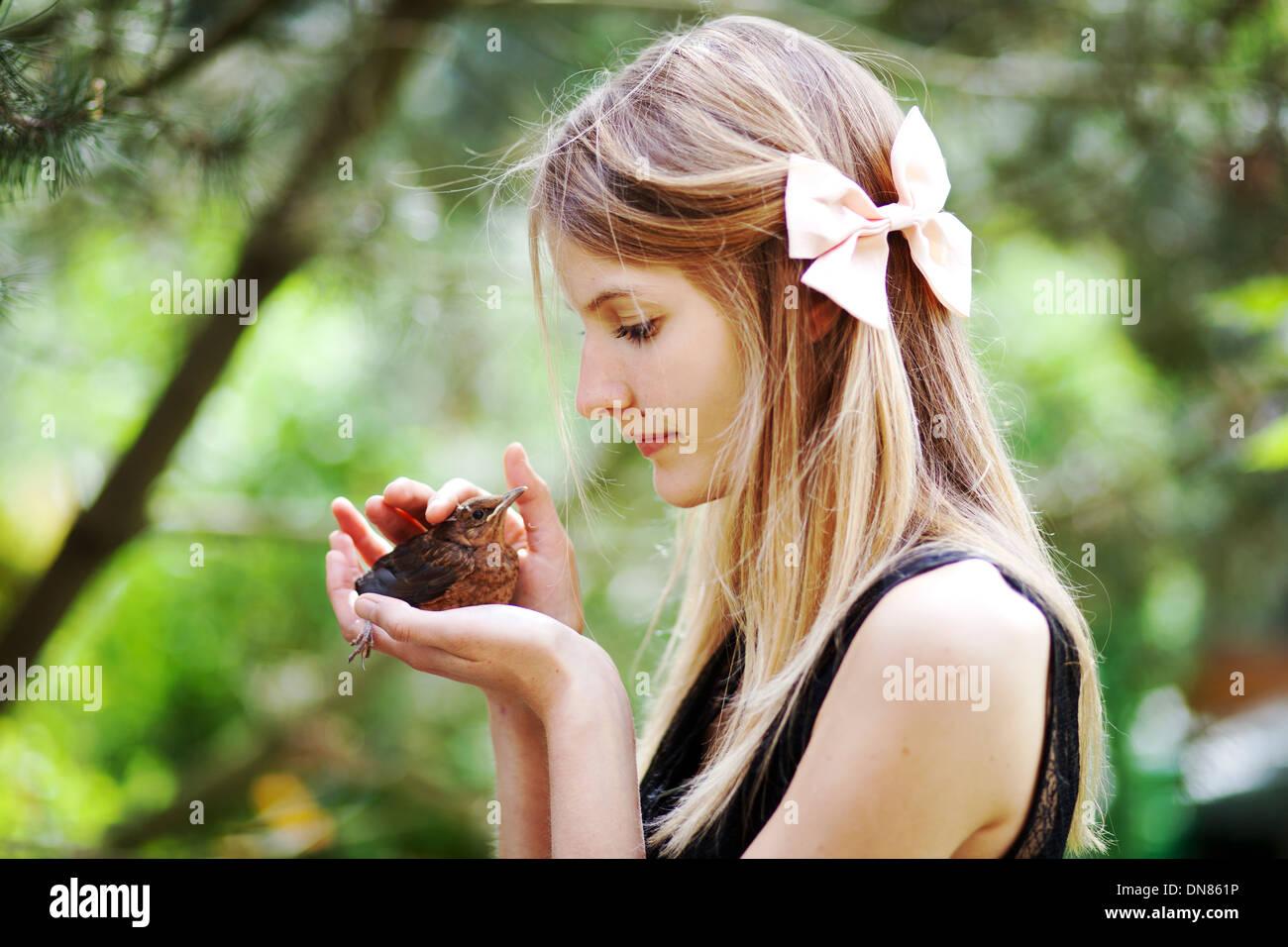 Chica con pájaro joven en la mano Imagen De Stock