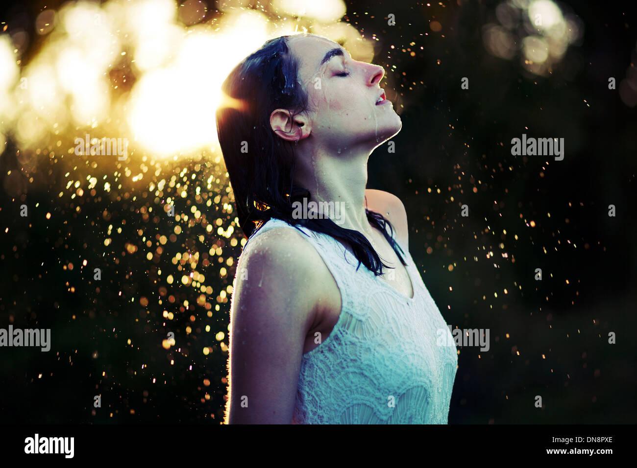 Mujer joven refrescante a sí misma en la lluvia Imagen De Stock
