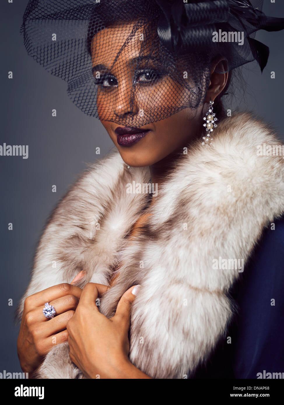 Belleza retrato de una sonriente joven negra vistiendo pieles y velo negro que le cubre el rostro Imagen De Stock