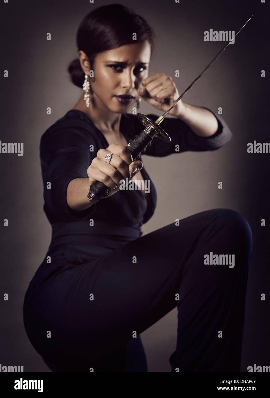 Joven negra con feroz expresión en una defensa de posar con un cuchillo, tanto japoneses espada corta en su mano Imagen De Stock