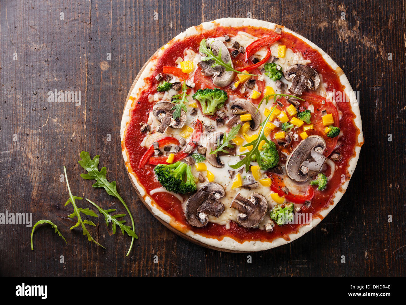 Pizza vegetariana con setas y rucola sobre mesa de madera Imagen De Stock