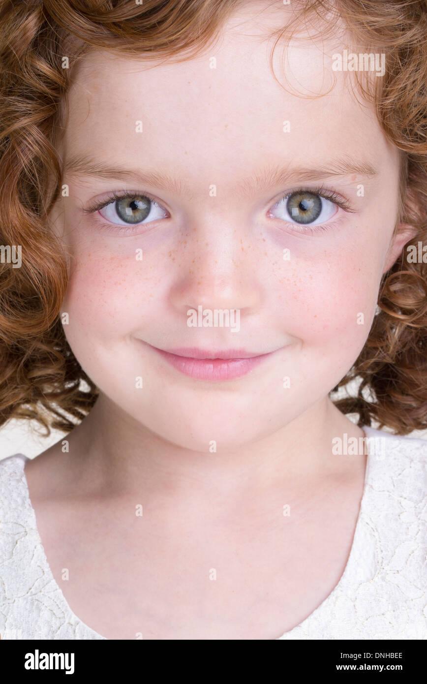 Close Up retrato de sonriente joven chica con pelo rojo rizado similar al de Annie Foto de stock