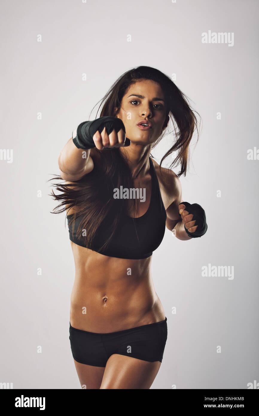 Colocar joven perforando hacia la cámara contra un fondo gris. Oriente Medio boxer hembra practicar boxeo. Foto de stock