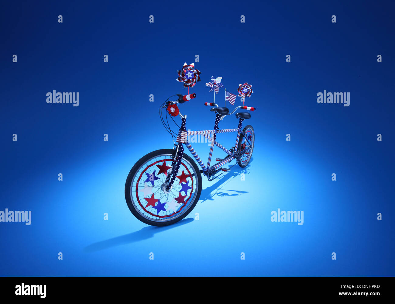 Un gemelo sentado bicicleta con adornos de color azul rojo y blanco sobre un fondo azul. Imagen De Stock