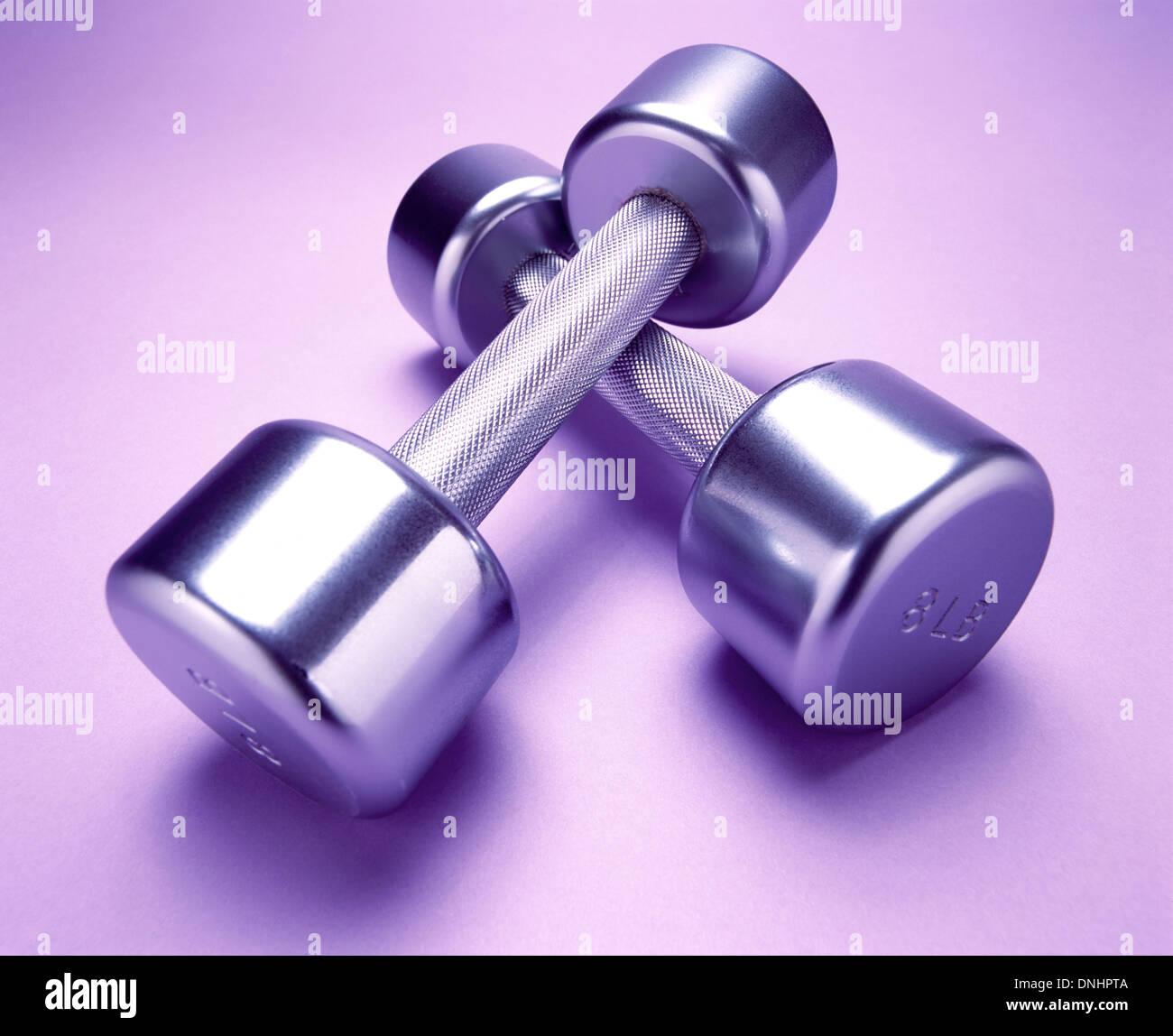 Un par de ejercicios de pesas de metal en una luz púrpura colchoneta de ejercicios. Imagen De Stock