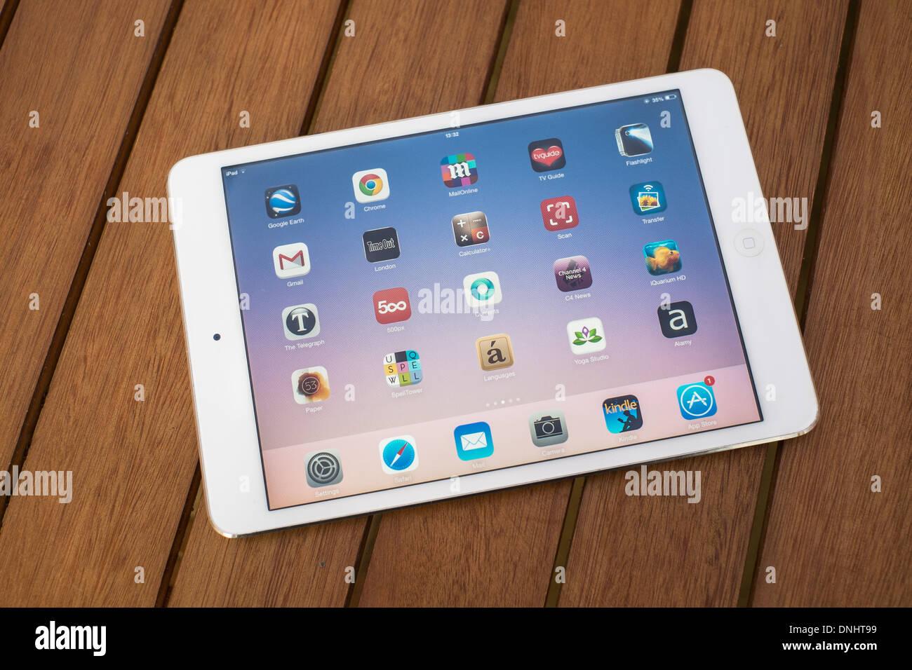 Mini Ipad blanco sobre una mesa de madera, mostrando la pantalla de Apps. Imagen De Stock