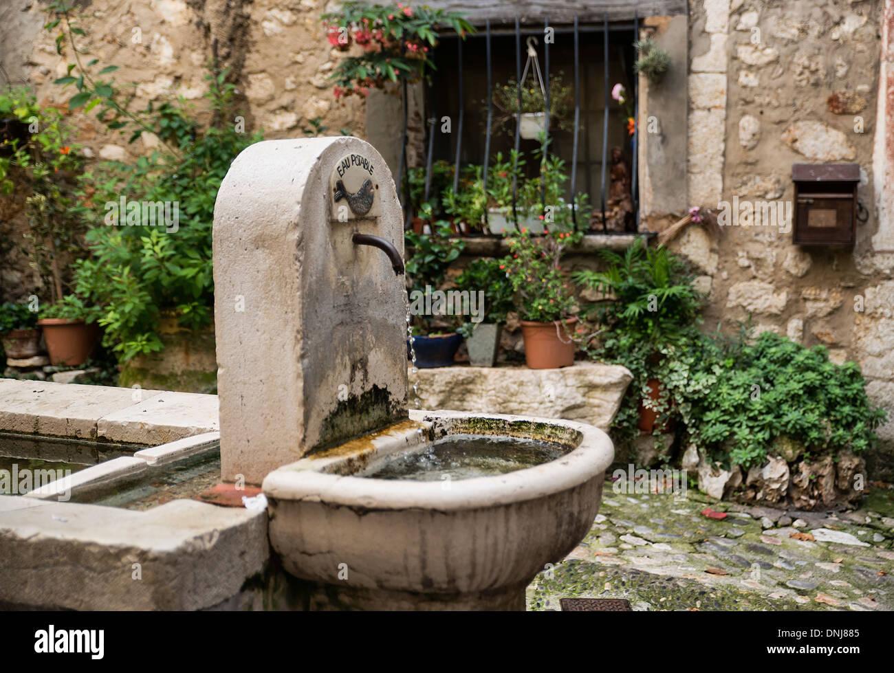 Una fuente de agua de estilo rústico en un patio en el pueblo de St Paul de Vence, Provenza, Francia Imagen De Stock
