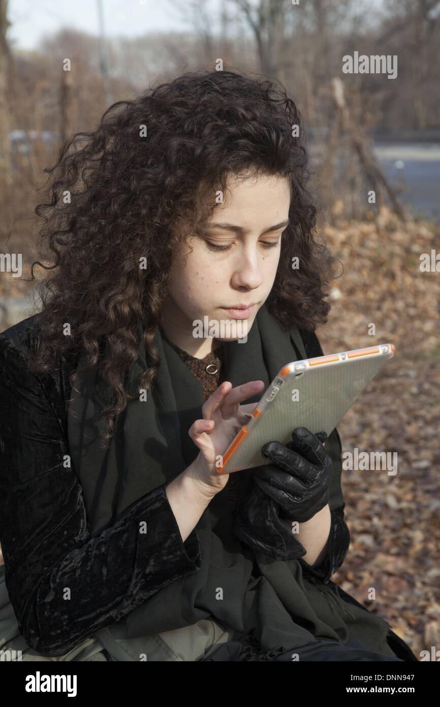 Mujer joven utiliza su ipad mini tablet, sentado en el parque de Brooklyn, NY. Imagen De Stock