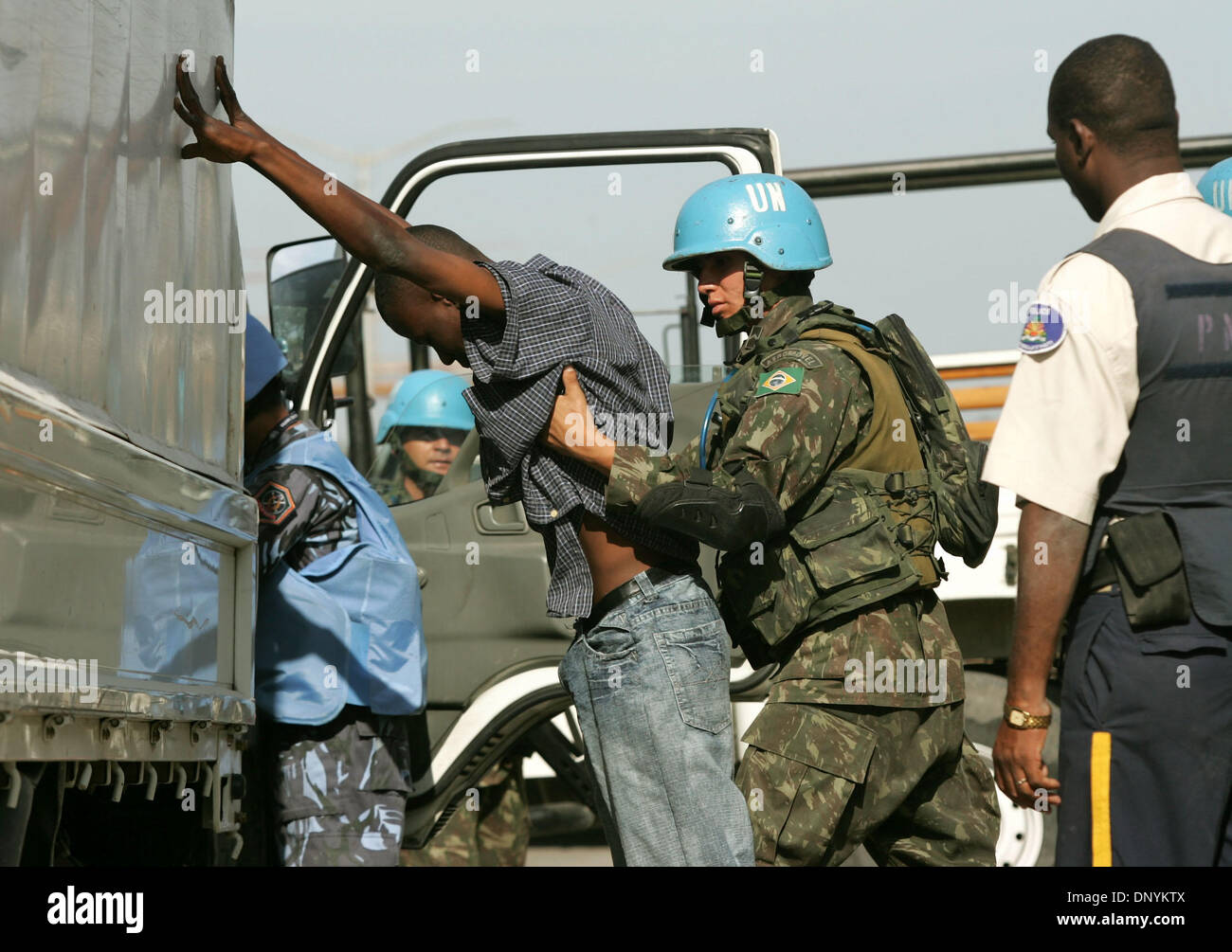 03 Feb, 2006; Port-au-Prince, Haití; los soldados de las Naciones Unidas, respaldado por la policía haitiana, para inspeccionar los vehículos y sus ocupantes en una carretera bloack cerca del barrio de Cité Soleil. El barrio se ha convertido en un bastión de las pandillas opuestos a la ONU, y un santuario para los secuestradores que ocultar a sus víctimas en su interior. Elecciones en Haití, la primera desde el derrocamiento violento del Presidente Jean-Bertrand AR Imagen De Stock