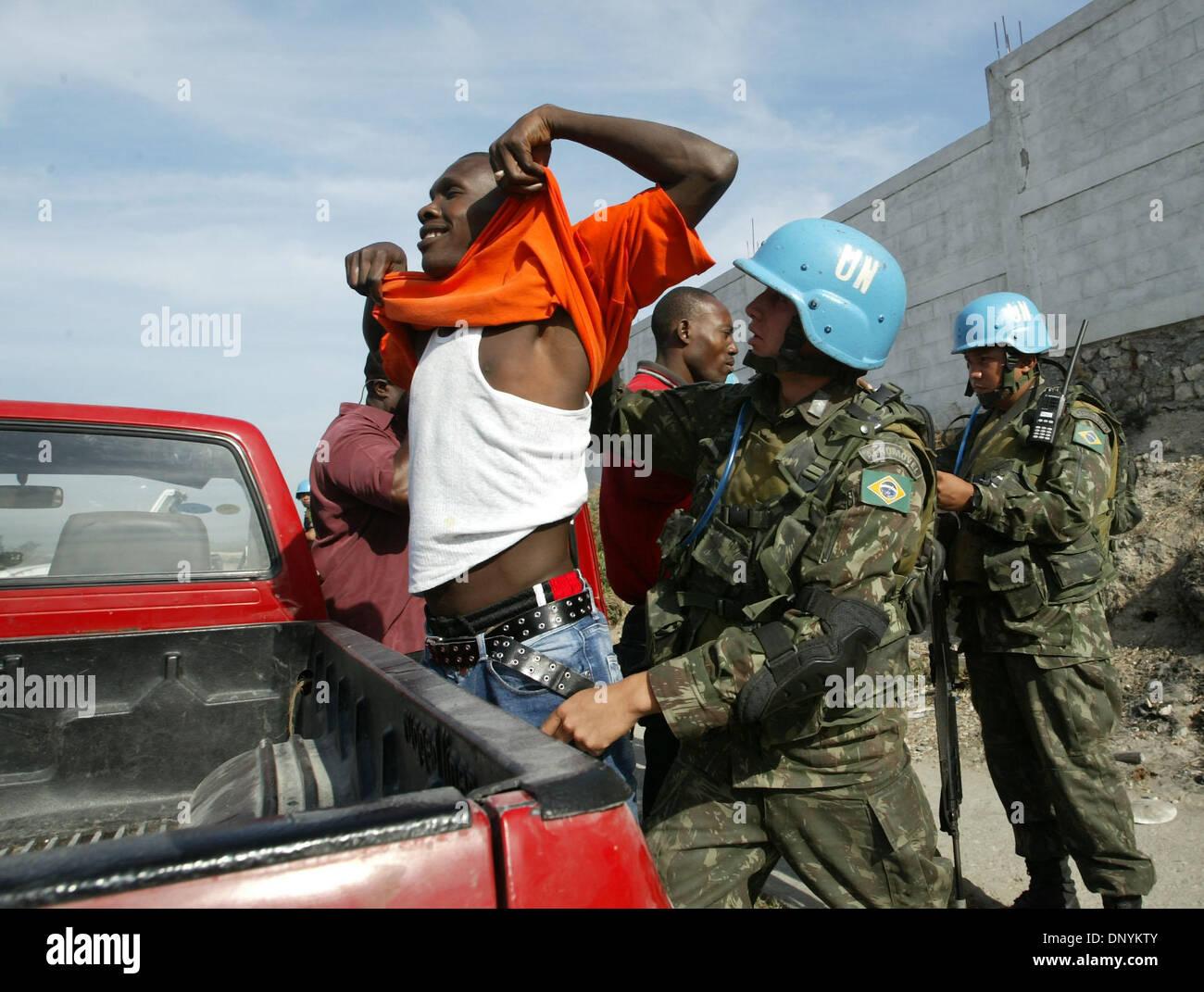 03 Feb, 2006; Port-au-Prince, Haití; los soldados de las Naciones Unidas buscar vehículos y sus ocupantes en una carretera bloack cerca del barrio de Cité Soleil. El barrio se ha convertido en un bastión de las pandillas opuestos a la ONU, y un santuario para los secuestradores que ocultar a sus víctimas en su interior. Elecciones en Haití, la primera desde el violento derrocamiento del Presidente Jean-Bertrand Aristide, están programados para la Fe Imagen De Stock