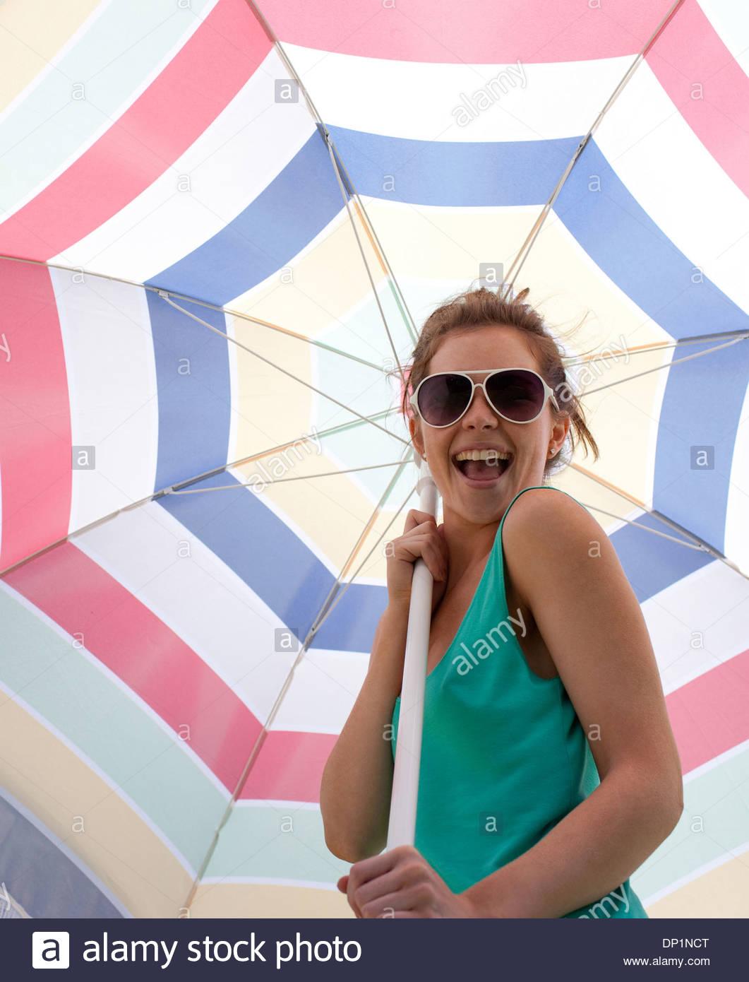 Mujer con gafas de sol la celebración de sombrilla en la playa Imagen De Stock