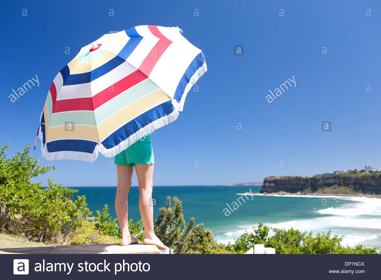Mujer en la playa la celebración de paraguas Imagen De Stock