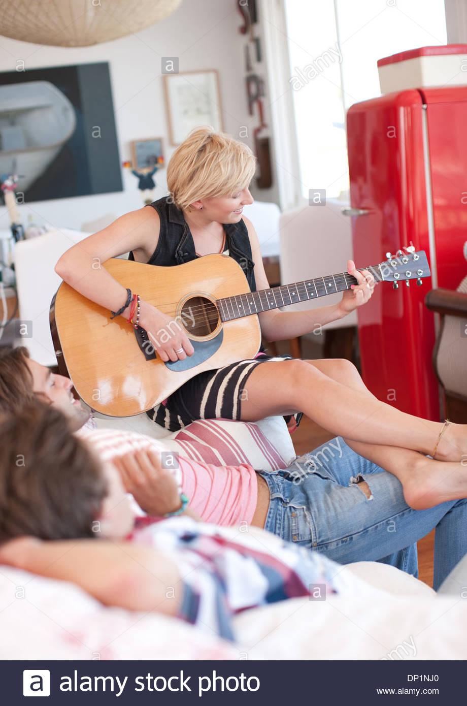 Mujer con los pies descalzos tocando la guitarra para hombres en el sofá Imagen De Stock