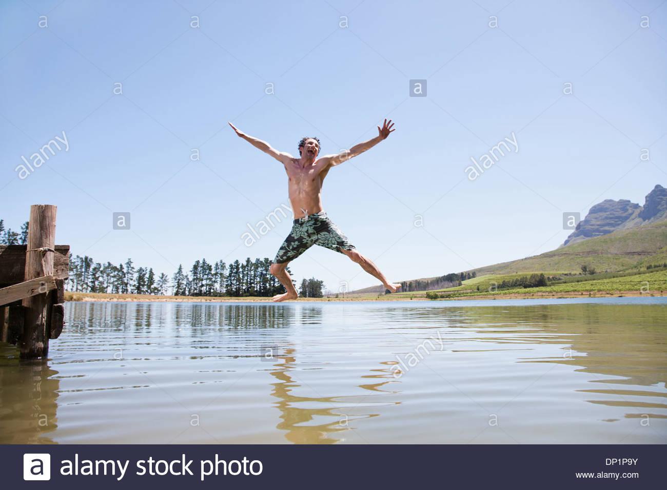 Hombre saltando de dock en el lago Imagen De Stock