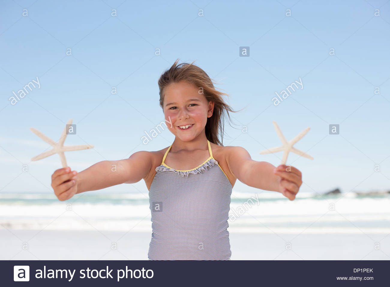 Chica sujetando starfish en la playa Imagen De Stock