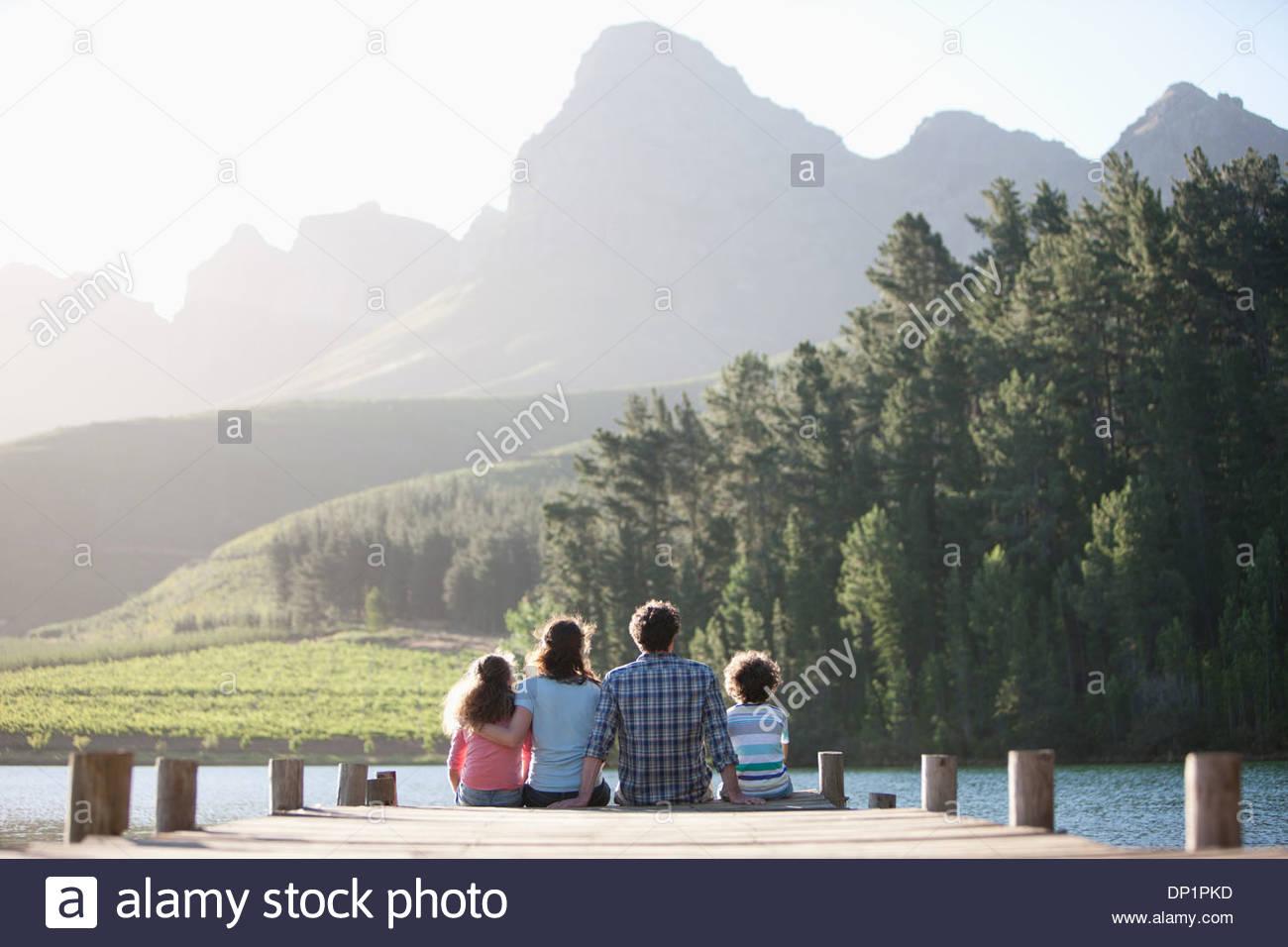 Familia sentada sobre el lago dock Imagen De Stock