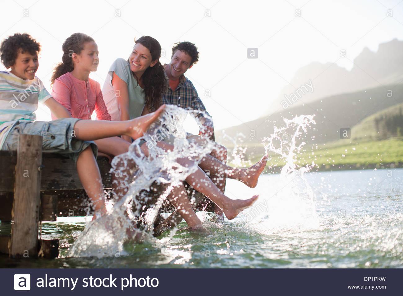 En el muelle de la familia salpicaduras de pies en el lago Imagen De Stock