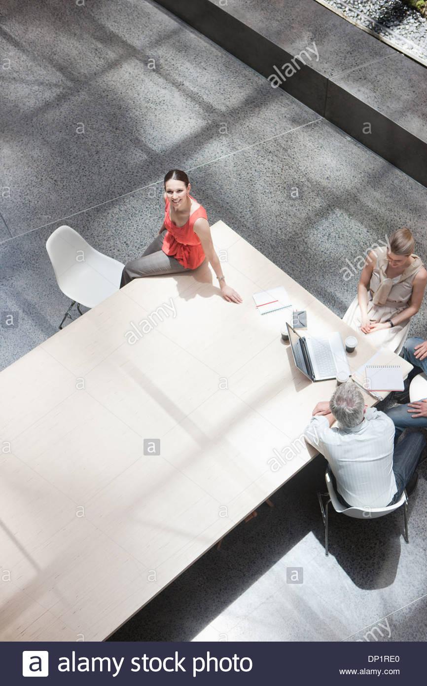 La empresaria trabajando aparte de co-trabajadores de mesa de conferencia Imagen De Stock