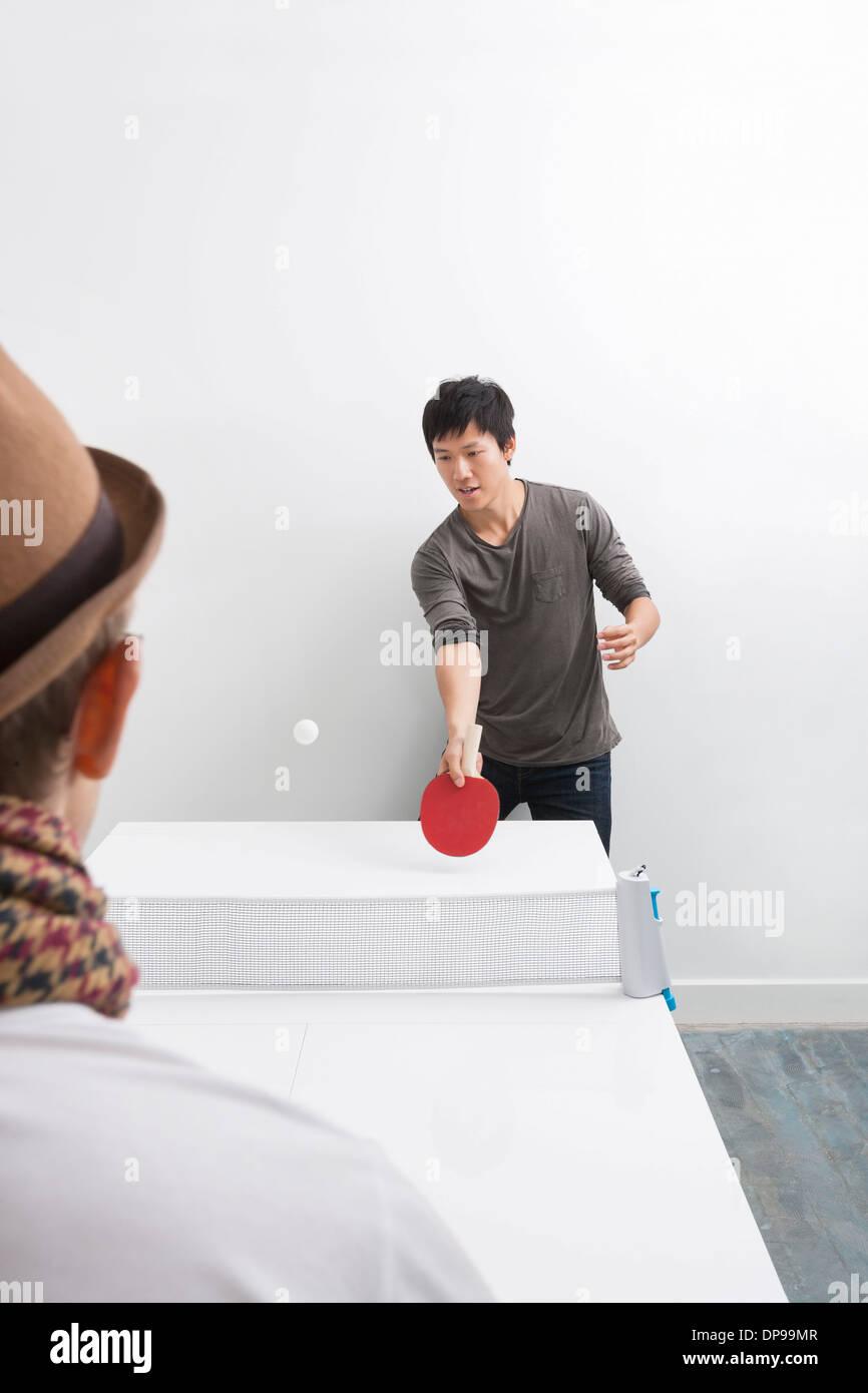 Mitad hombre adulto jugando al tenis de mesa con un amigo Imagen De Stock