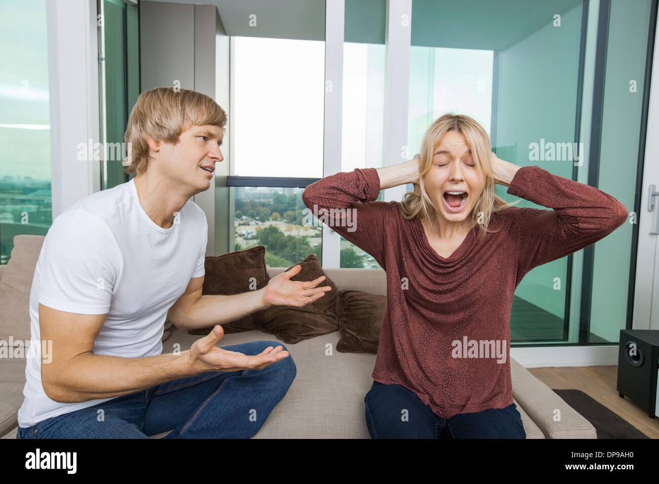 El hombre tratando de hablar como una mujer grita en voz alta en el salón en casa Imagen De Stock