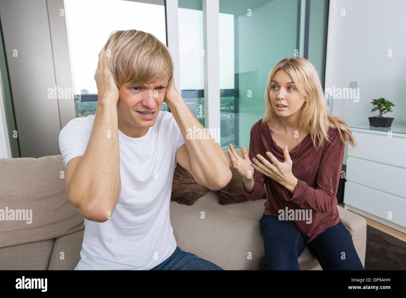Mujer tratando de hablar como hombre grita en voz alta en el salón en casa Imagen De Stock