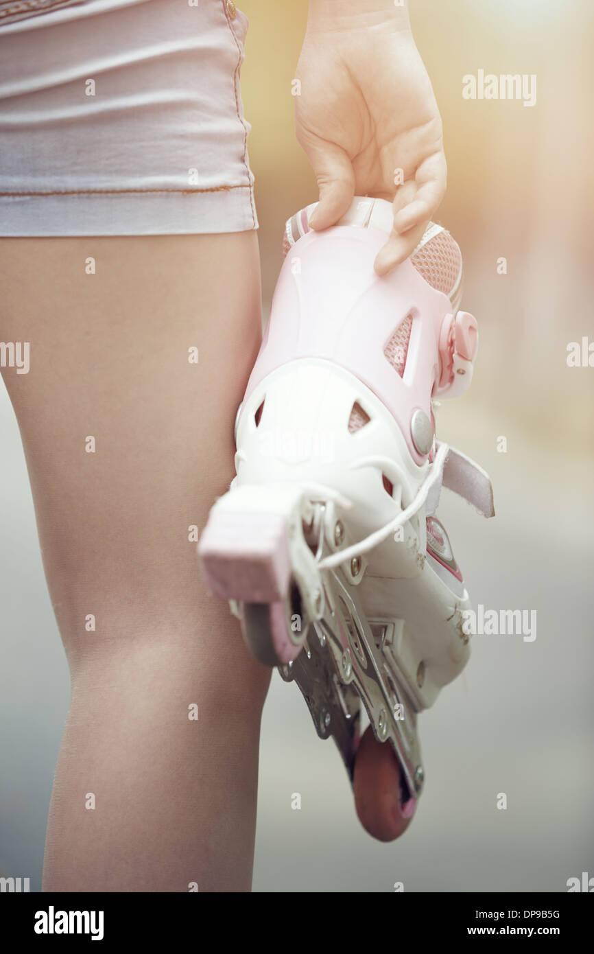 Vista cercana de adolescente la celebración de patines Imagen De Stock