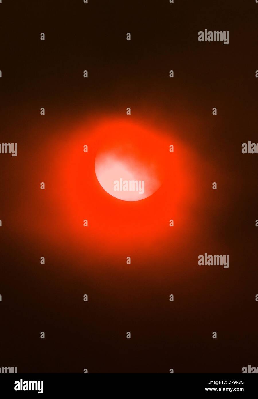 El humo de los incendios de bosques crea un inusual misterioso halo naranja a la puesta de sol. Imagen De Stock