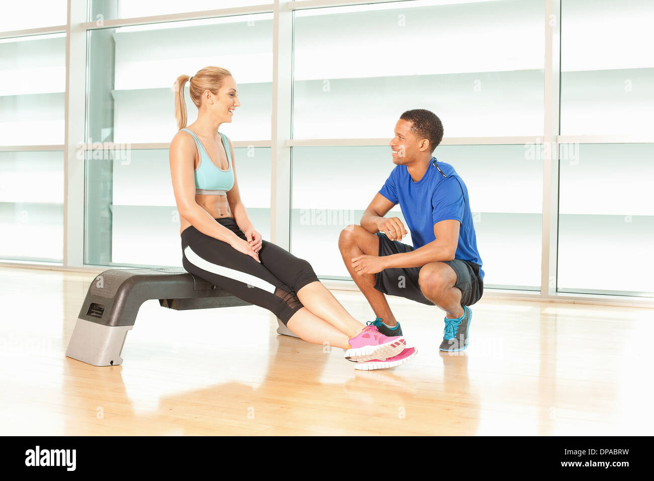 Mujer sentada sobre ejercicio paso hablando con instructor de fitness Imagen De Stock