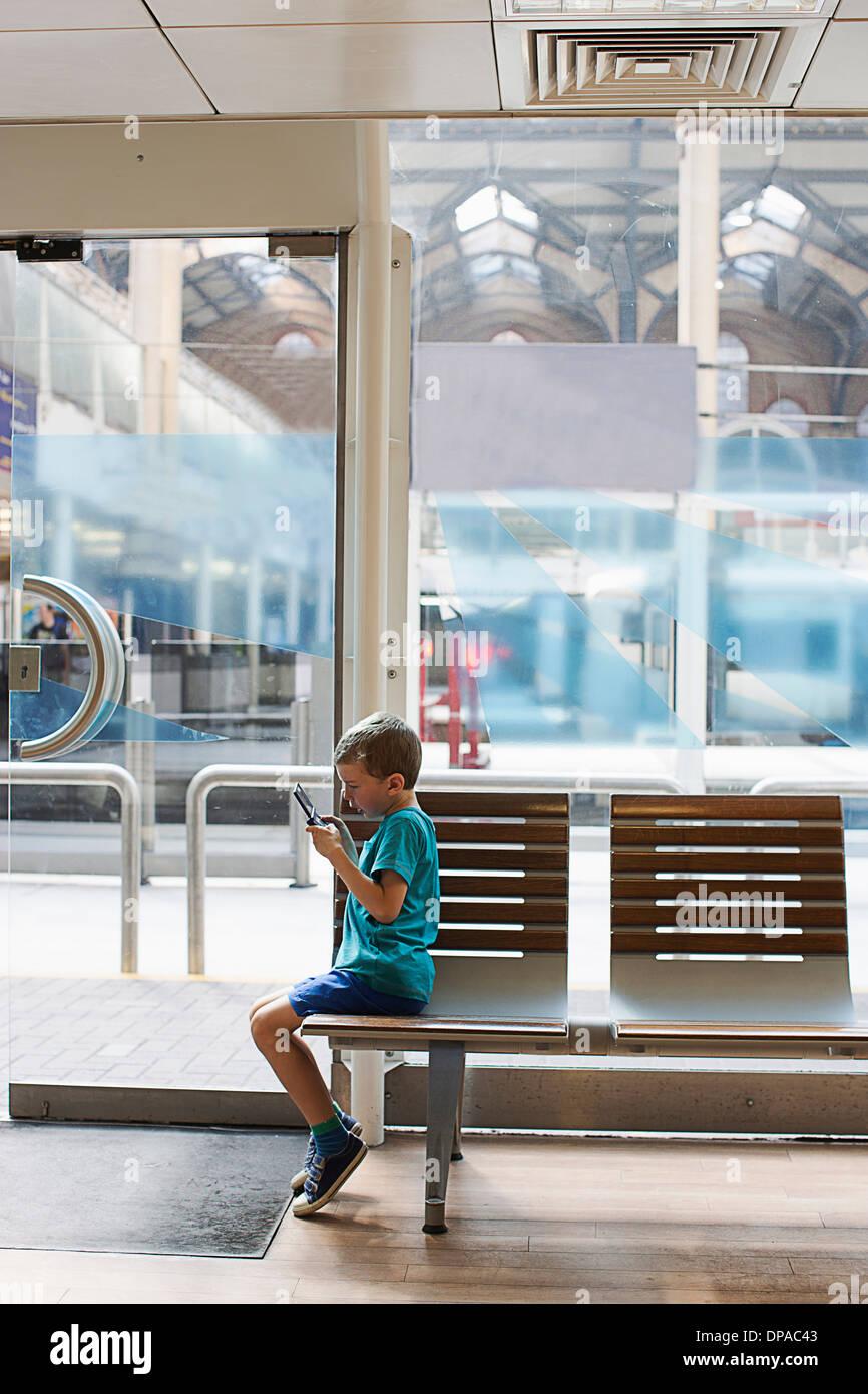 La estación de tren de joven en la sala de espera jugando juegos electrónicos Imagen De Stock