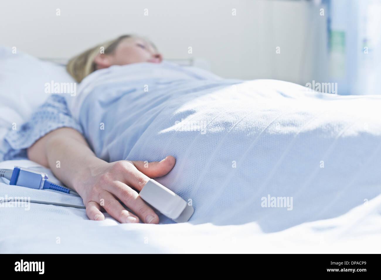 Paciente acostado en la cama de un hospital con monitor en el dedo Imagen De Stock