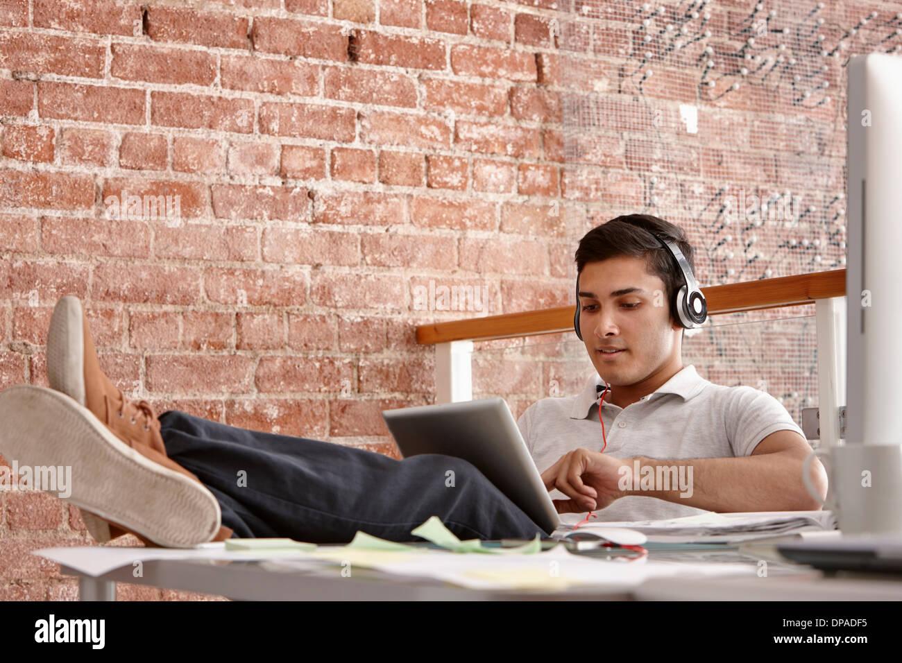 Joven mediante tableta digital usando audífonos, pies arriba Imagen De Stock