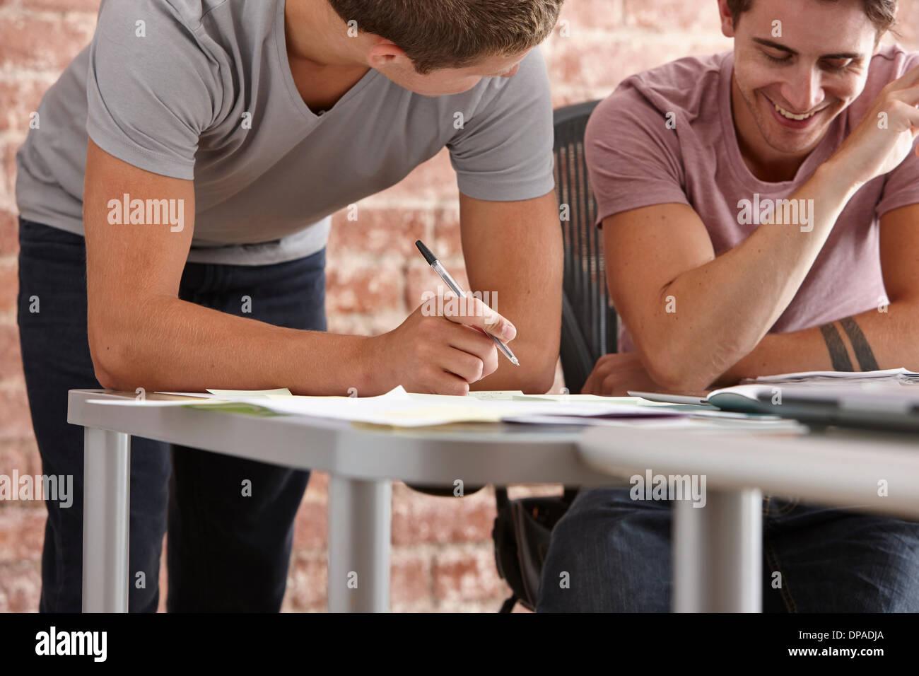 Dos colegas masculinos, uno haciendo notas Imagen De Stock