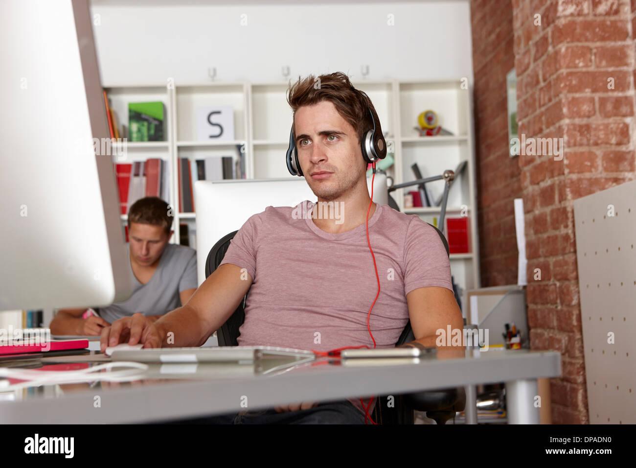 Joven en el trabajo usando audífonos Imagen De Stock