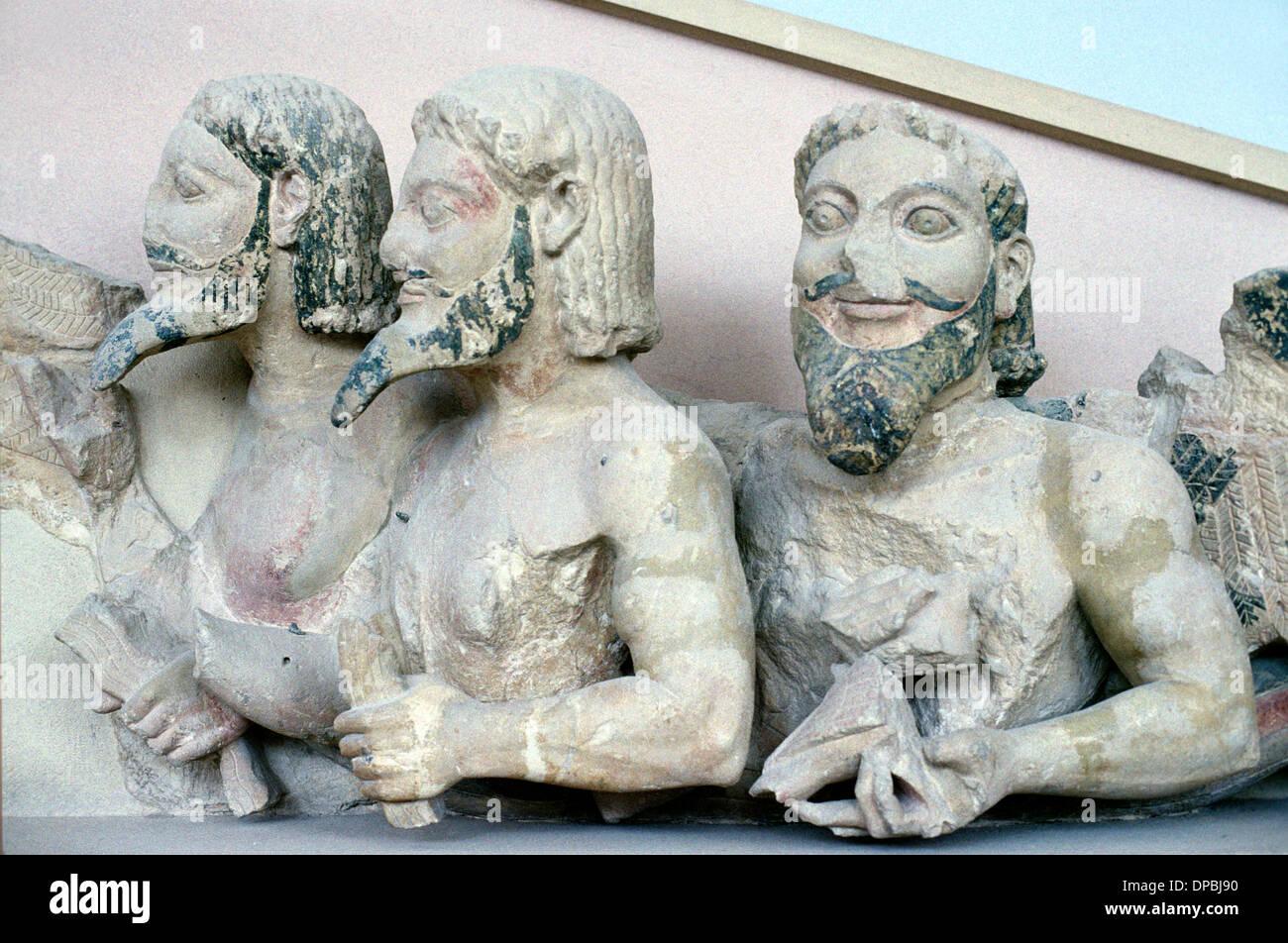 Tres cuerpo monstruo barbudo en el frontón de c6th BC templo griego en piedra porosa Foto de stock