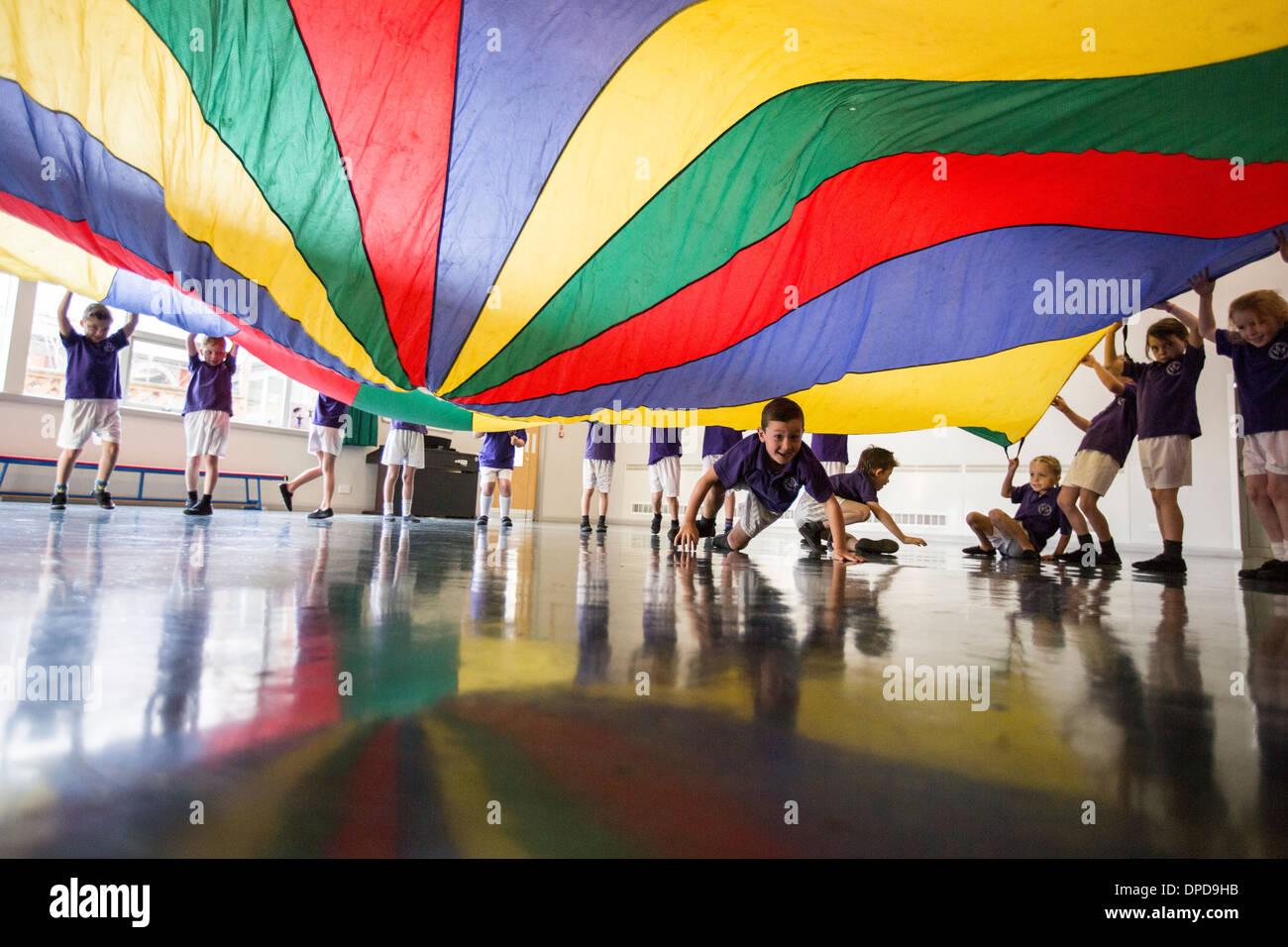 Los alumnos de una escuela primaria del Reino Unido jugando con un paracaídas en el pasillo de la escuela Imagen De Stock