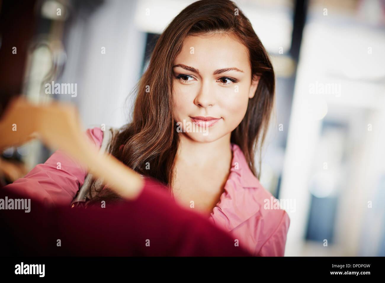 Mujer joven busca rosa en el colgador superior Foto de stock