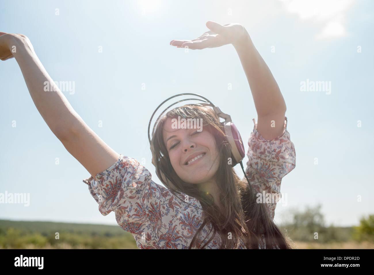 Retrato de mujer adulta media bailando en el campo usando audífonos con los brazos levantados Imagen De Stock
