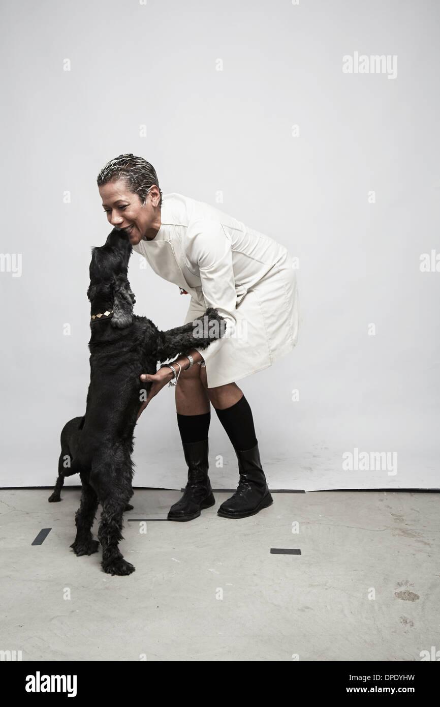 Foto de estudio de la mujer madura, divertirse con perros Imagen De Stock