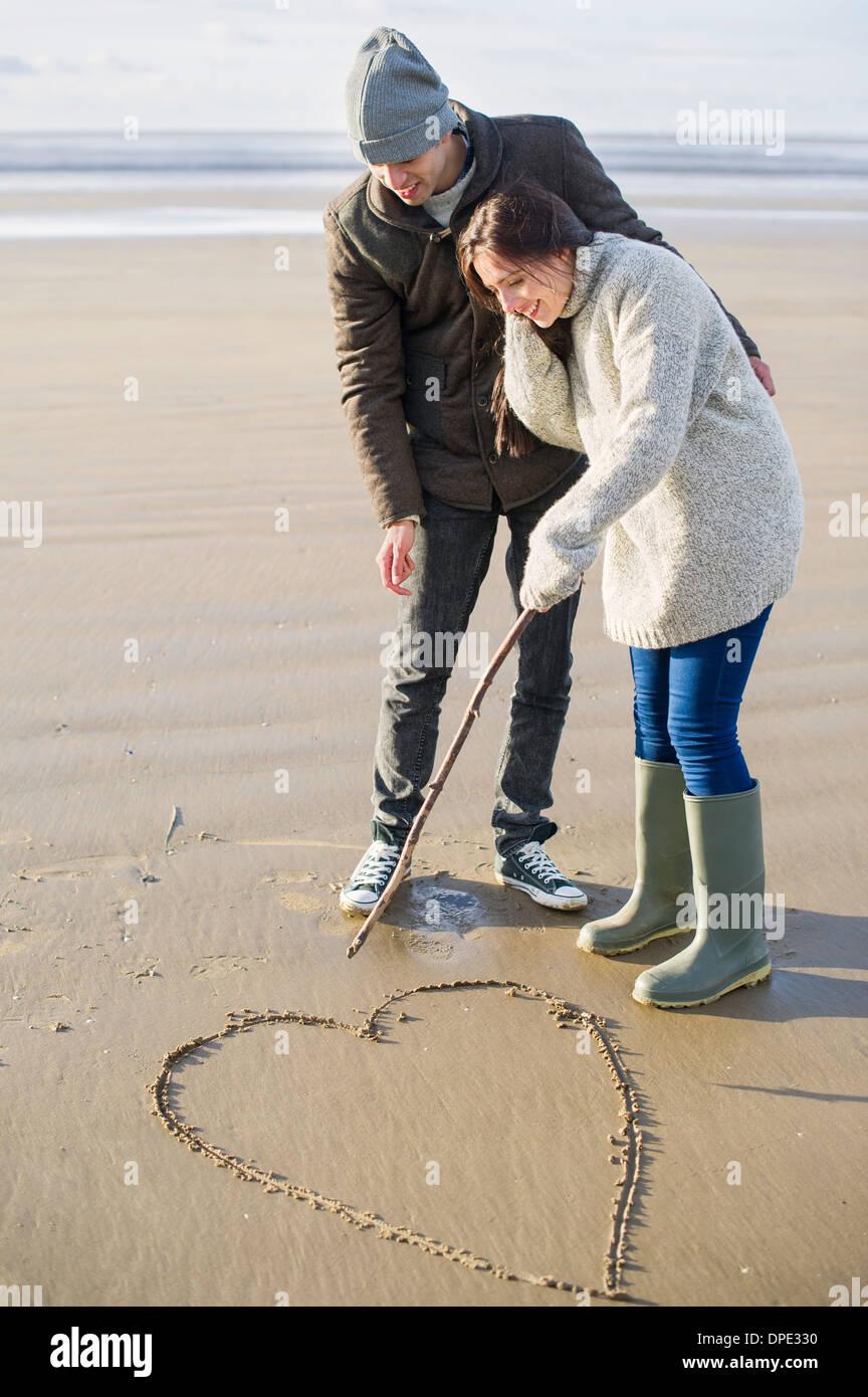 Pareja joven corazón dibujo en la arena, Brean Sands, Somerset, Inglaterra Imagen De Stock